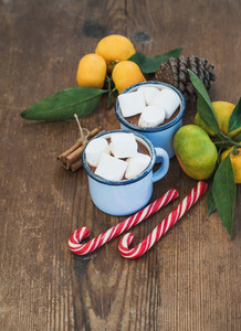 Hot chocolate in enamel metal mugs  fresh mandarins  cinnamon sticks  pine cone and candy canes over rustic wooden background
