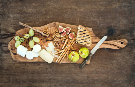 Wine appetizers set  cheese selection  honey  grapes  almonds  walnuts  bread sticks  figs on olive wood serving board over rustic background  horizontal
