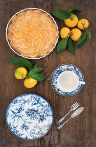 Homemade tangerine pie  fresh fruit and porcelain dinnerware over rustic wooden background