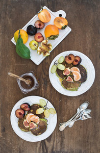 Breakfast set  Homemade zucchini pancakes with fresh plum  tangerine  grapes  figs and honey in white ceramic plates over rustic wooden background