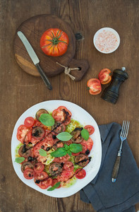 Ripe village heirloom tomato salad with olive oil  basil and spices over rustic wooden background