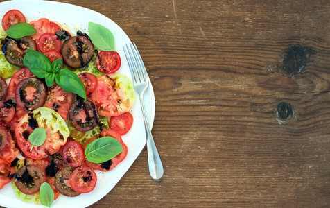 Ripe village heirloom tomato salad with olive oil and basil over rustic wooden background top view