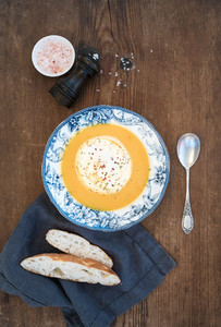 Homemade pumpkin cream soup in porcelain plate with spices and fresh bread slices on over rustic wooden background