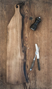 Kitchen ware set  Old rustic serving board  knive and fork  pepperbox on a old wooden background
