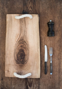 Kitchen ware set  Old rustic serving board tray  knive and fork  pepperbox on a old wooden background