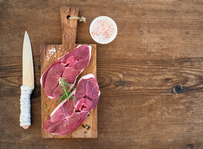 Raw fresh meat lamb entrecote and seasonings on cutting board over rustic wooden background