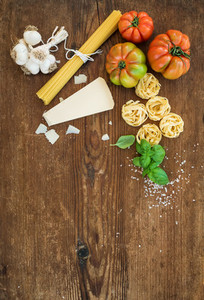 Ingredients for cooking pasta  Spaghetti  tagliatelle  garlic  Parmesan cheese  tomatoes and fresh basil on rustic wooden background  top view  copy space