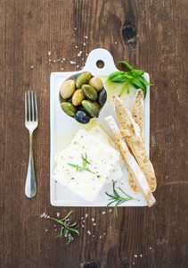 Fresh feta cheese with olives  basil  rosemary and bread slices on white ceramic serving board over rustic wooden background
