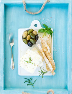 Fresh feta cheese with olives  basil  rosemary and bread slices on white ceramic serving board over bright turquoise blue painted wooden background