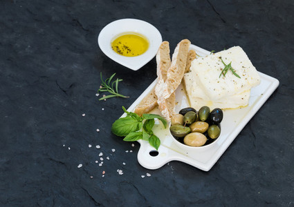 Fresh feta cheese with olives  basil  rosemary and bread slices on white ceramic serving board over black slate stone background