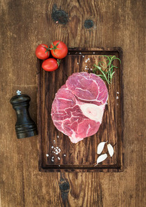 Raw fresh beef meat cross cut for ossobuco with garlic cloves  cherry tomatoes  rosemary  pepper and salt on serving board over rustic wooden background