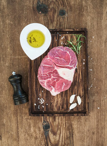 Raw fresh beef meat cross cut for ossobuco with garlic cloves  rosemary  pepper  oil and salt on serving board over rustic wooden background