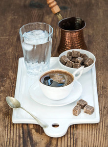 Cup of black coffee copper pot water with ice in glass and cane sugar cubes on white ceramic serving board over rustic wooden backdrop