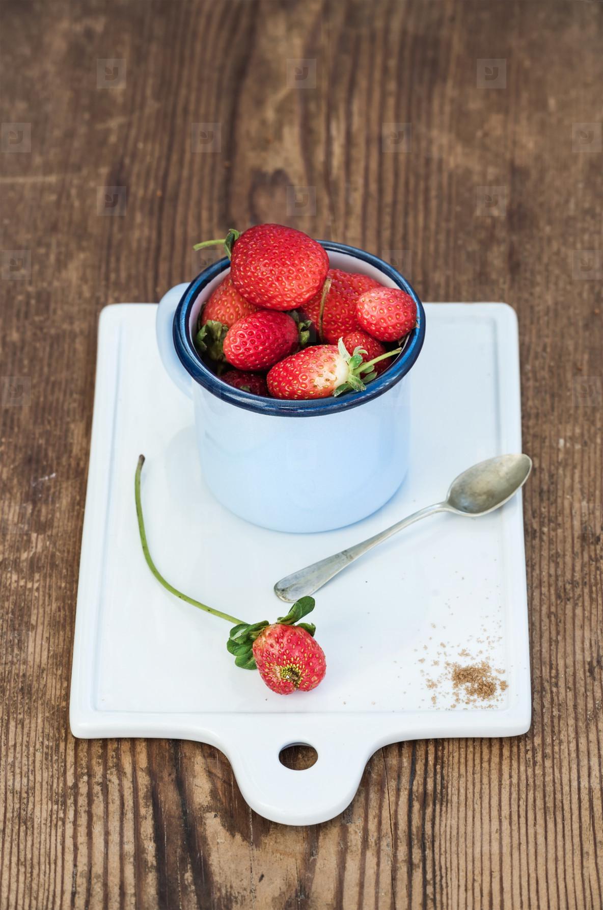 Fresh ripe red strawberries in blue enamel mug on white ceramic board over rustic wooden background