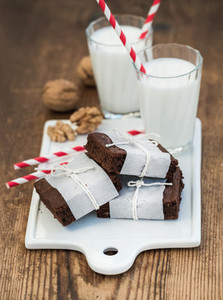 Chocolate brownie slices wrapped in paper and tired with rope  glasses of milk  stripe straws  walnuts on white ceramic board over rustic wooden background