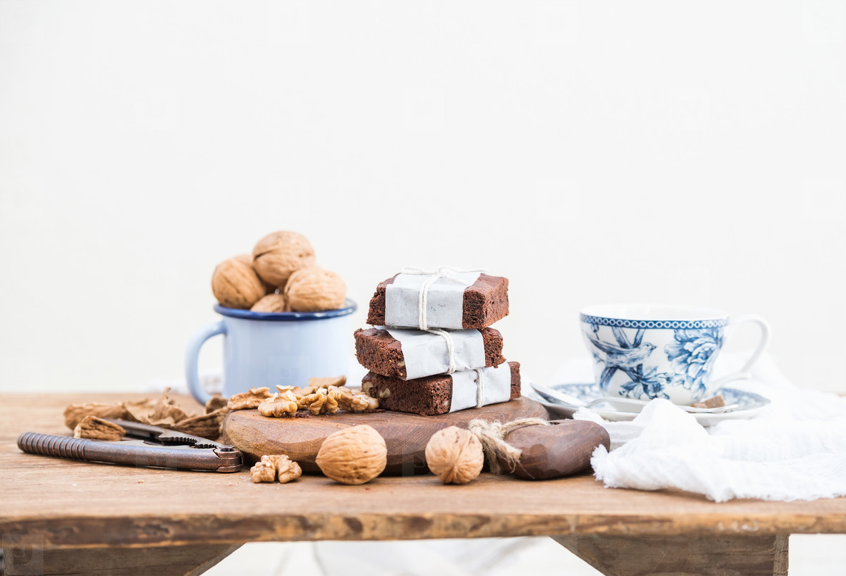 Chocolate brownie slices wrapped in paper and tired with rope  porcelain tea cup  enamel mug of walnuts on rustic wooden table  white background