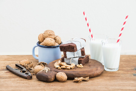 Chocolate brownie slices wrapped in paper and tired with rope  milk glasses  stripe straws  enamel mug of walnuts on rustic wooden table  white background