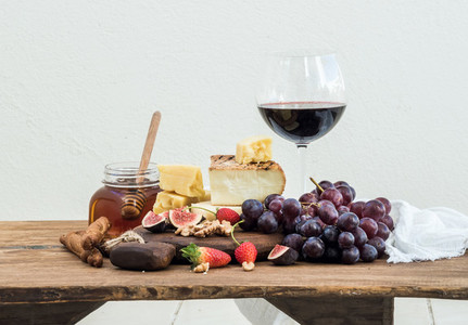 Glass of red wine  cheese board  grapes fig  strawberries  honey and bread sticks  on rustic wooden table  white background
