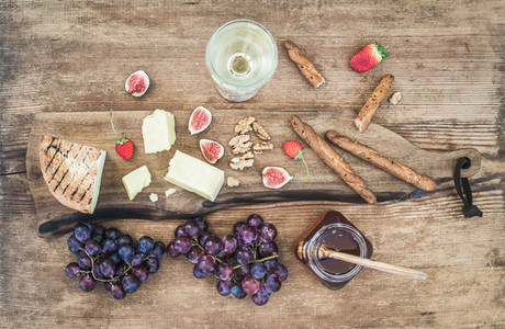 Glass of white wine  cheese board  grapes  figs  strawberries  honey and bread sticks on rustic wooden background
