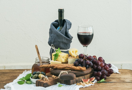 Glass of red wine cheese board grapes fig strawberries honey and bread sticks  on rustic wooden table light background