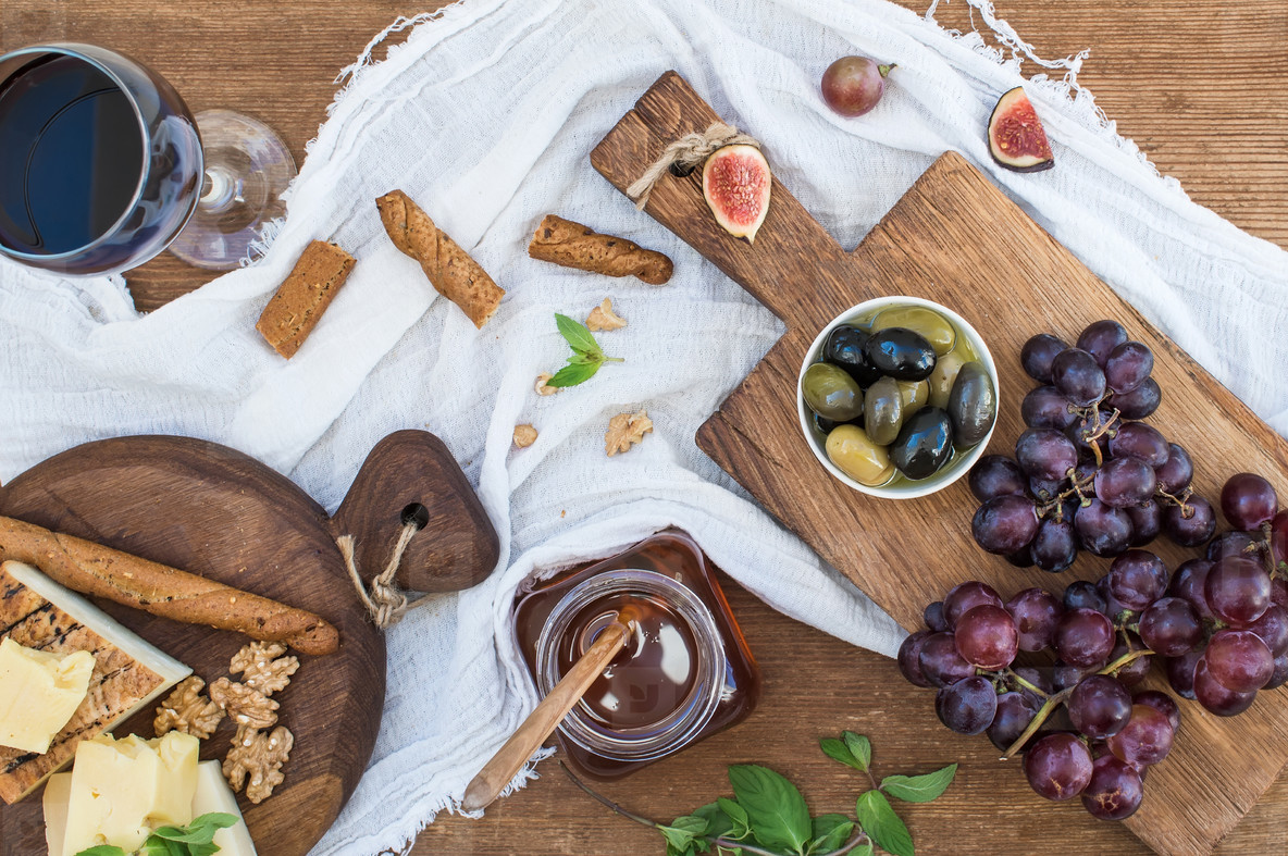 Glass of red wine  cheese board  grapes  walnuts  olives  honey and bread sticks