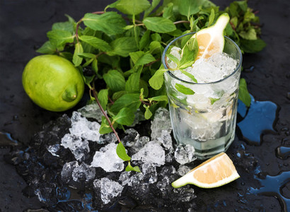 Mojito cooking set Bunch of fresh mint lime chipped ice and coctail glass over black slate stone backdrop