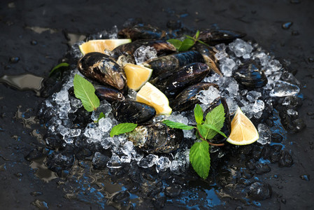 Fresh uncooked mussels with lemon  herbs and spices on chipped ice over dark slate stone backdrop