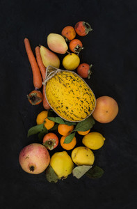 Mixed yellow orange fruit and veggies assortment  ingredients for smoothie  Melon  garnet  grapefruit  carrot  persimmon  lemon  quince  pear over black slate stone background