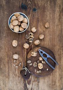 Walnuts in ceramic bowl and on cutting board with nutcracker over  rustic wooden background  top view