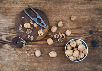 Walnuts in ceramic bowl and on cutting board with nutcracker