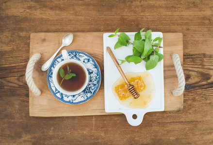 Cup of herbal tea with fresh mint and honey on wooden tray over rustic background  Top view