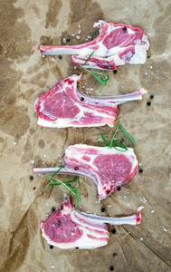 Rack of Lamb with rosemary and spices over oily craft paper background