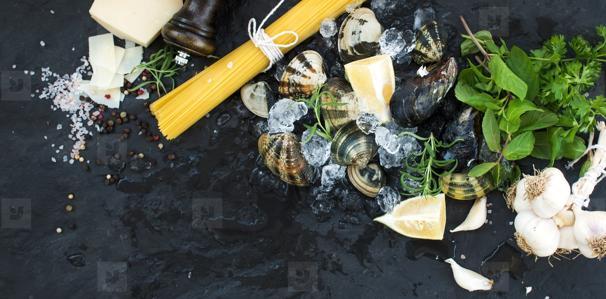 Ingredients for cooking Spaghetti vongole  Clams on chipped ice  raw pasta  Parmesan cheese  garlic  parsley and lemon over stone slate background  top view