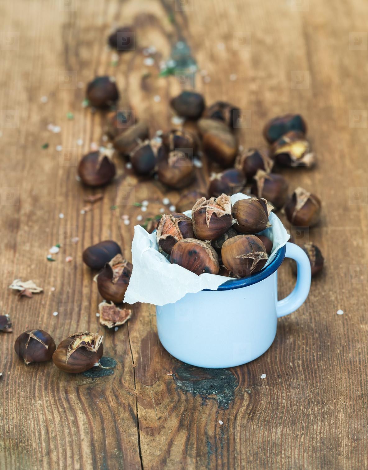 Roasted chestnuts in blue enamel mug on rustic wooden background  selective focus