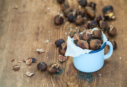 Roasted chestnuts in blue enamel mug on rustic wooden background  selective focus