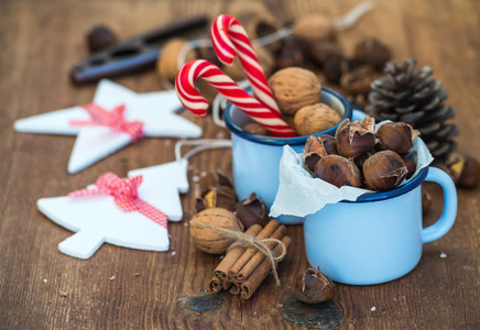 Traditional Christmas foods and decoration  Roasted chestnuts in blue  enamel mug  walnuts  cinnamon sticks  candy canes  pine cone on rustic wooden background