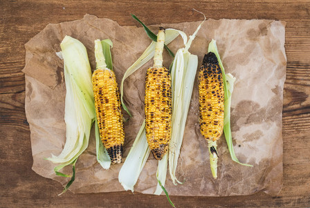Grilled corn over oily craft paper and rustic wooden background  top view