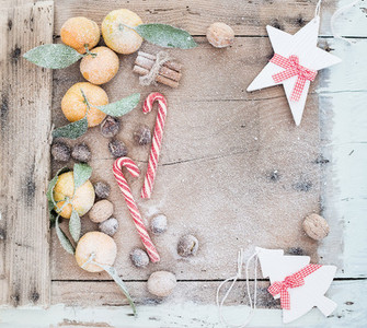 Christmas or New Year frame Fresh mandarins cinnamon sticks walnuts roasted chestnuts and candy canes covered with snow over rustic wooden background top view