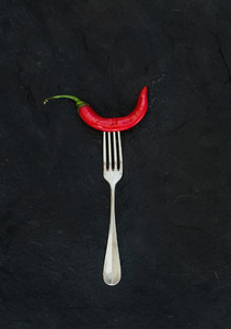 Red hot chili pepper on vintage silver fork over black slate stone background  top view