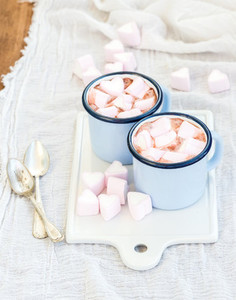 Saint Valentines holiday greeting set Hot chocolate and heart shaped marshmallows in old enamel mugs on white ceramic serving board