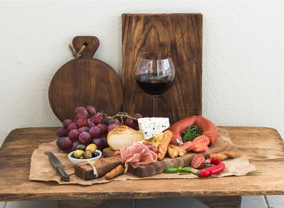 Glass of red wine  cheese and meat board  grapes fig  strawberries  honey  bread sticks  on rustic wooden table  white background