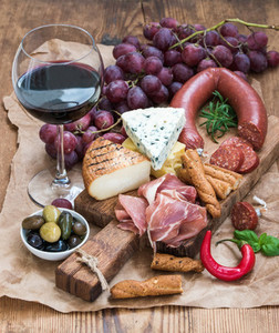 Glass of red wine cheese and meat board grapesfig strawberries honey bread sticks  on rustic wooden table white background