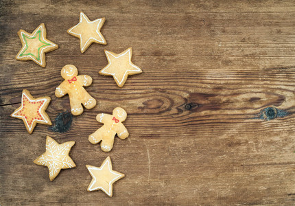 Christmas homemade gingerbread cookies of man and stars over rustic wooden background top view