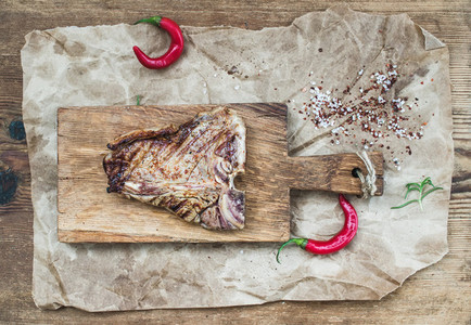 Cooked meat t bone steak on serving board with red chili peppers