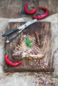 Cooked meat t bone steak on serving board with red chili peppers  spices  fresh rosemary over oily craft paper and rustic wooden background  selective focus