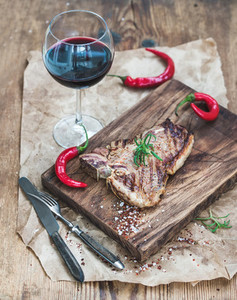 Cooked meat t bone steak on serving board with roasted tomatoes