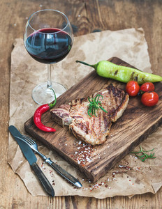Cooked meat t bone steak on serving board with roasted tomatoes  charlestone green pepper  chili  fresh rosemary  spices and glass of red wine over rustic wooden background