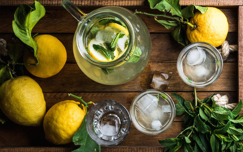 Homemade mint lemonade served with fresh lemons and ice over wooden background