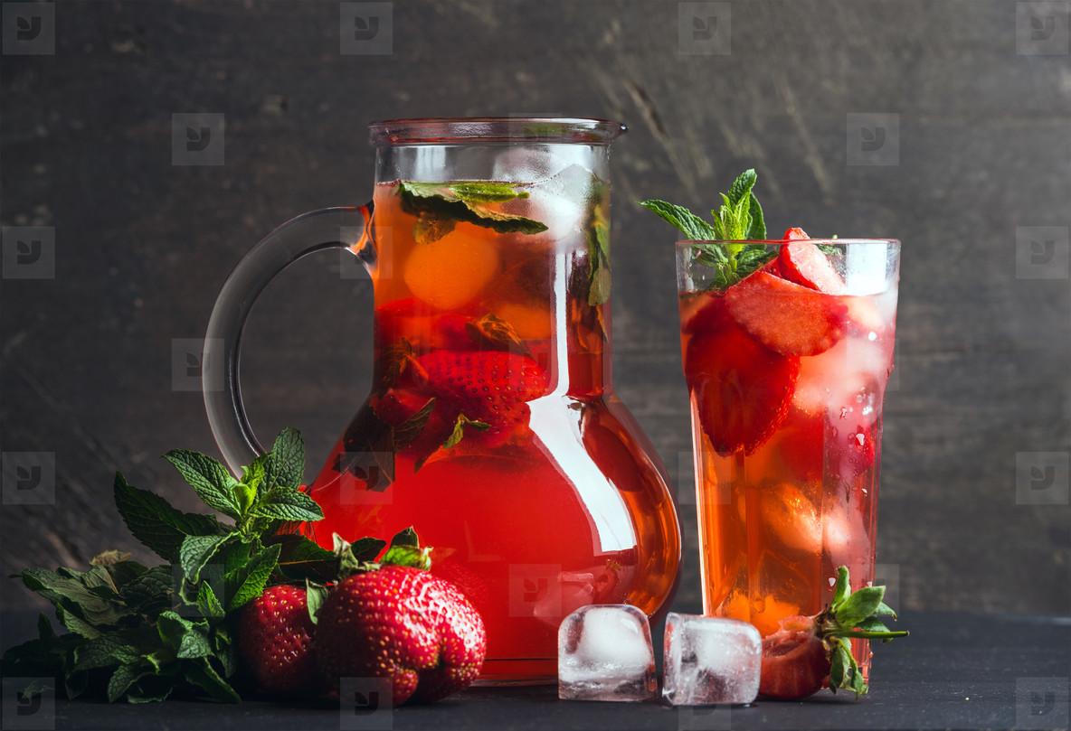 Homemade mint strawberry lemonade on dark wooden background