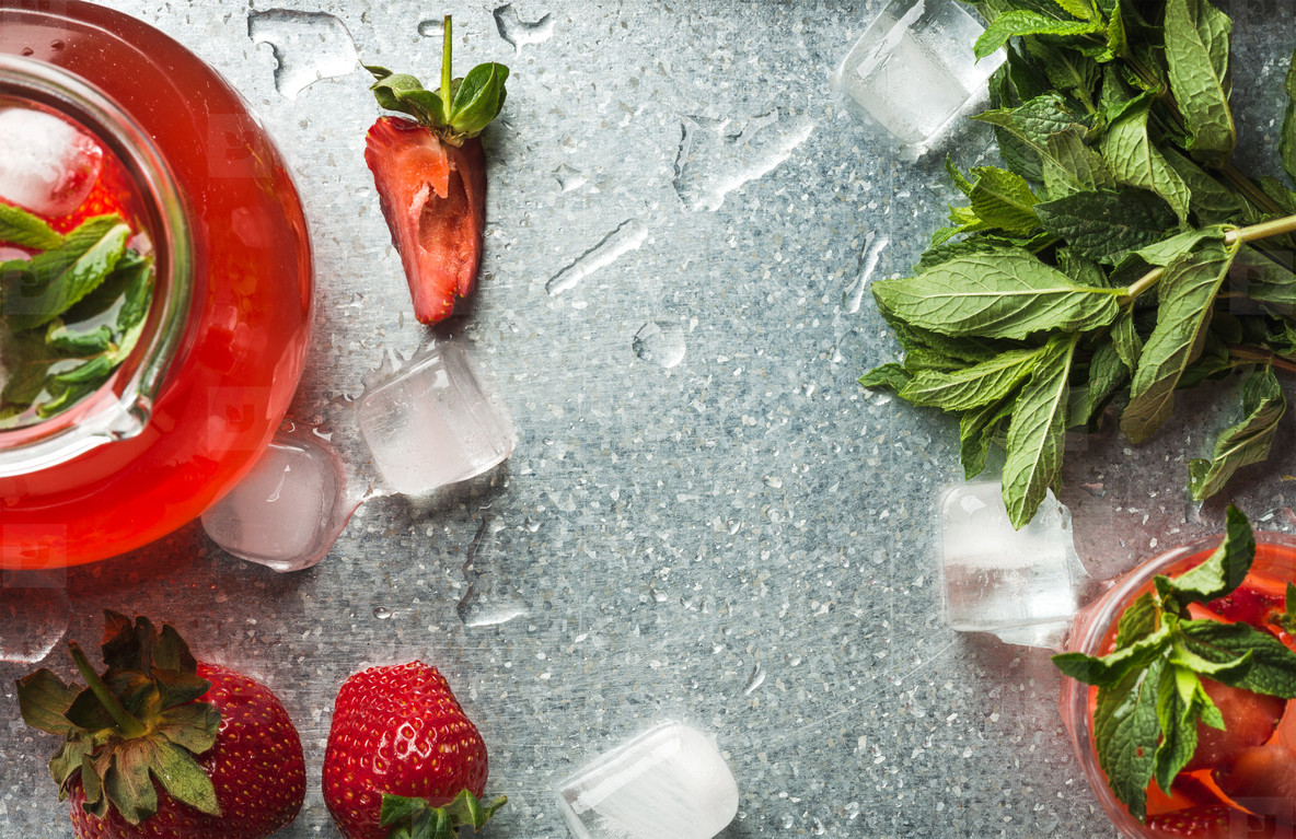 Homemade strawberry lemonade with mint  ice and fresh berries over metal tray background  top view  copy space